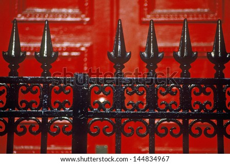 Detail of wrought iron gate and red door of boarding school, New York City, NY