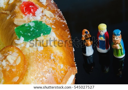 Detail on a kings cake and three figurines that can be found hidden into it. Roscon de reyes or rosca de reyes with surprises