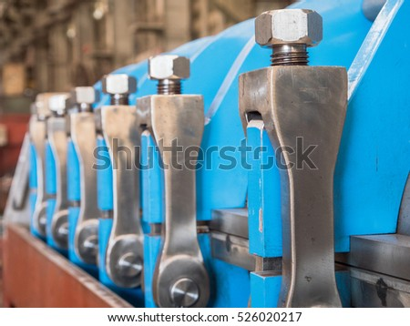 Detail photo of twin screw industrial press for processing, of food byproducts. Shallow depth of field with the first lock in focus.