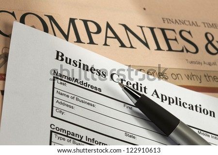 Detail shot of a business credit application with a pen and news paper.