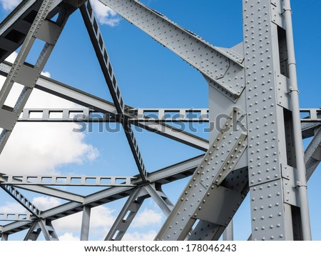 Detail shot of an historic gray painted Dutch riveted truss bridge against a blue sky.