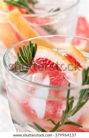 detox water with grapefruit and rosemary, ice in glasses on a white wooden background
