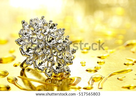 diamond ring on golden background with water drops