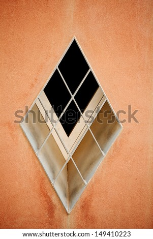 Diamond shaped abstract windows on an ochre coloured wall