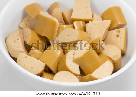 Diced boiled sausage in white ceramic bowl over white background. Isolated image of sausage or ham in white ceramic bowl on white.