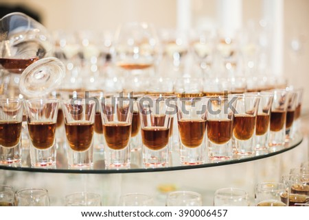 Different alcohol drinks in goblets and wine glasses on wedding buffet table