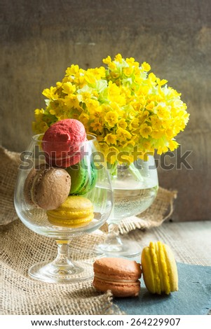 Different color of macaroon sweets on the old table
