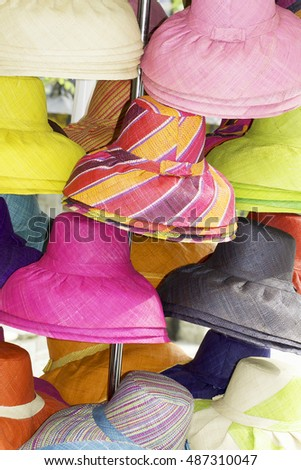different coloured beach hats in a street shop