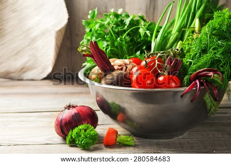Different, home-grown fresh, young vegetables in an iron bowl, beets, green onions, bulb onion, cherry tomatoes, parsley, fennel, garlic, carrots lie on a wooden table. closeup. rustic style