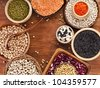 Different kinds of bean seeds, lentil, peas in dish on wooden desk - stock photo