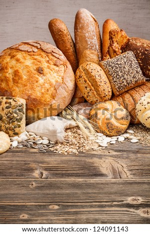 Different kinds of fresh bread on wooden table