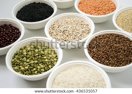 Different kinds of groats in small white bowls on white background
