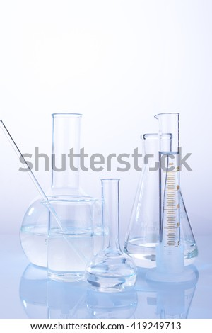 Different laboratory glassware with water and empty with reflection on white background