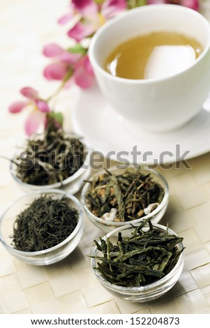 Different sorts of green tea with cup and cherry blossoms in the back, selective focus