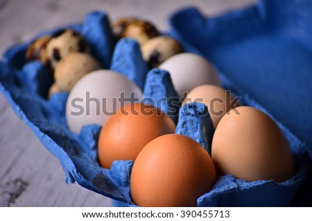 different types of eggs i on a old wooden background