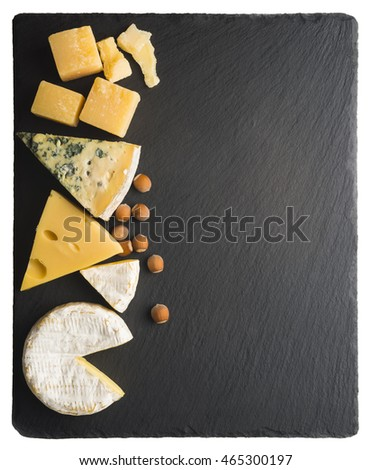 Different varieties of cheese on a black board.