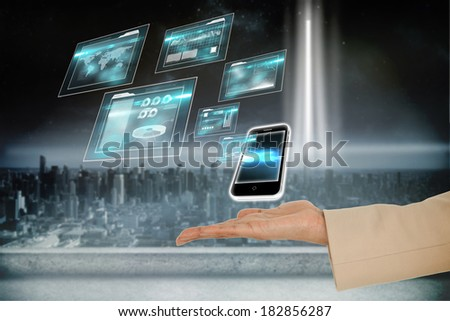 Digital composite of hand presenting smartphone and interfaces
