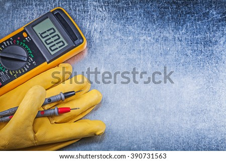 Digital electric tester safety gloves on metallic background electricity concept.
