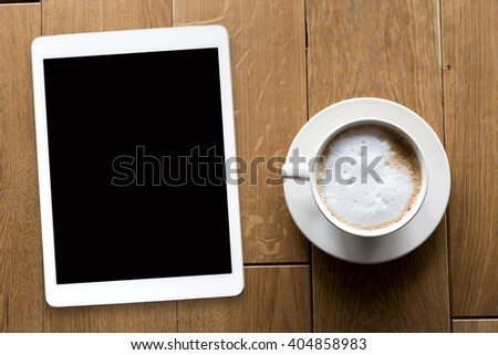 Digital tablet and coffee cup on wooden table, above view
