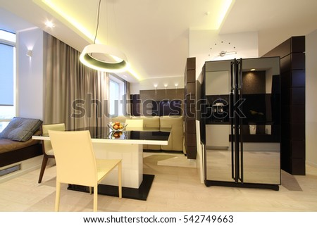 Dining area with a large table and chairs in front of recreation area with a home theater in modern flat