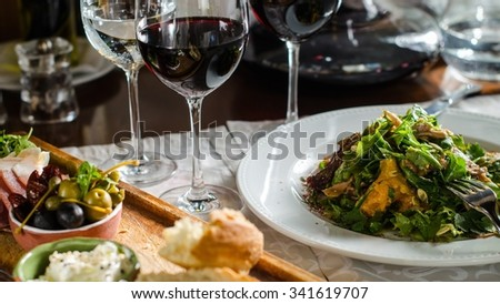 Dinner at the restaurant - wine, snacks and meat salad . Served table . Bread, cheese, olives, prosciutto, duck salad, red wine.