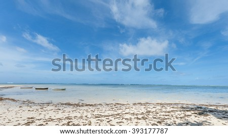 Dirty and Messy Beach in Seychelles with three boats and Indian Ocean Water. Weed on the sand