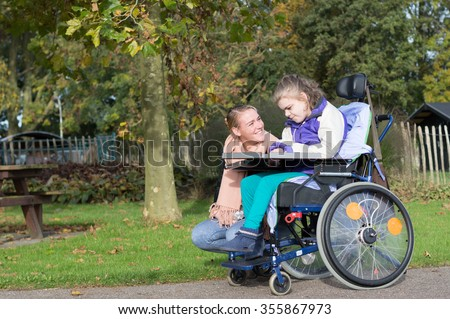 Disabled Child Wheelchair Relaxing Outside Together Stock