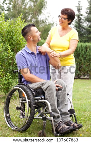 disabled young man in wheelchair with his mother on his side