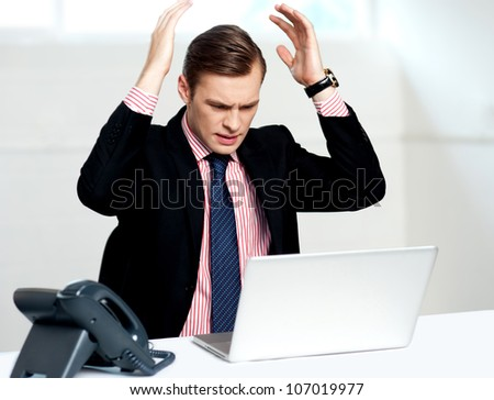 Disappointed businessman looking at laptop with hands above his head