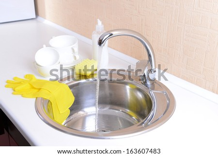 Dishes drying near  metal sink