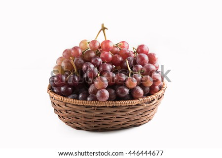 Display of bunches of fresh red grapes in a wicker basket