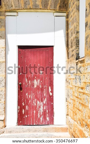 Distressed red wooden door with white framing and limestone brick/Red Door/Distressed with Limestone