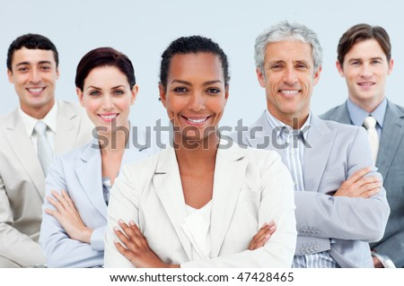 Diverse business people standing with folded arms smiling at the camera