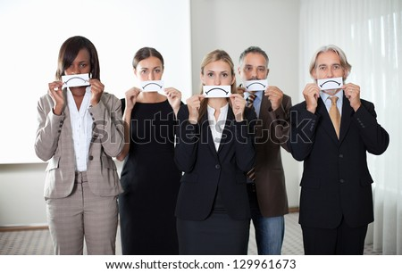 Diverse group of business people holding a card with sad sign by their faces