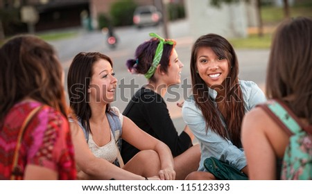 Diverse group of happy teenage girls sitting and talking