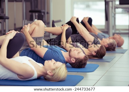 Diverse group of people in a gym class lying in a receding row on mats doing leg flexes in a health and fitness concept
