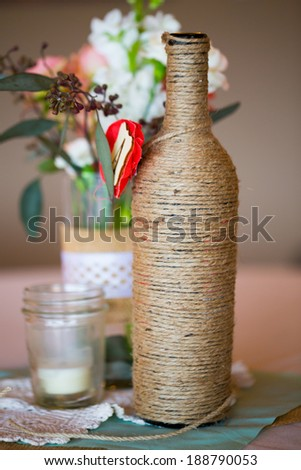 DIY Wedding Decor Table Centerpieces With Wine Bottles Wrapped In Burlap Twine And Rose Flowers
