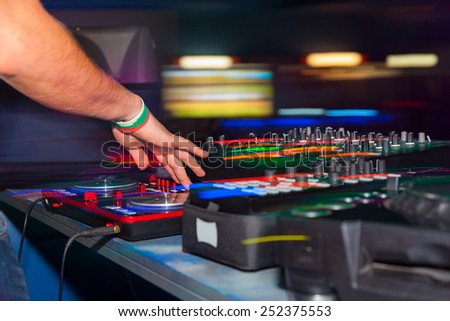 DJ hands on the remote. nightclub