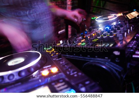 DJ playing music at mixer closeup and mixes the track in the nightclub at party