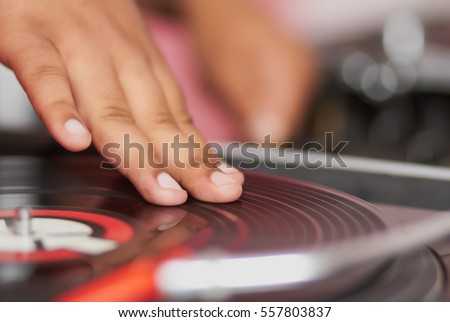 DJ scratch vinyl record on turntable.Professional records player in close up.Disc jockey mix music tracks on classic analog equipment.African guy play songs at party