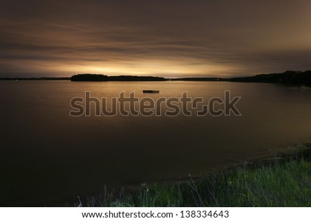 Dock floating in a bay at night with a glowing horizon, Maine, USA