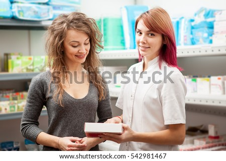 Doctor and client in warehouse looking at a boxe of pills