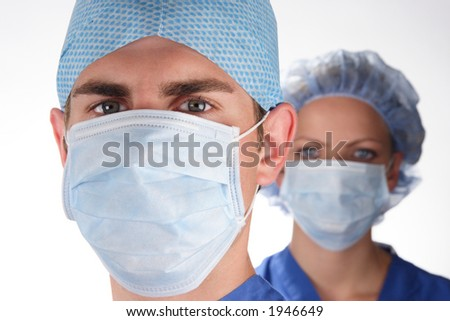 Doctor and nurse wearing surgical scrubs. Doctor in foreground. Shallow depth of field with nurse slightly out of focus in background.