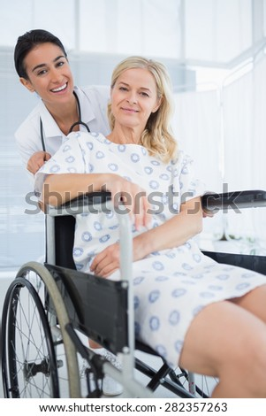 Doctor and patient in wheelchair smiling at camera in hospital