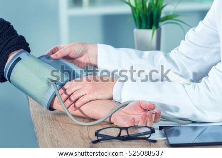 Doctor cardiologist measuring blood pressure of female patient in hospital office, health care control and monitoring.