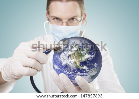 Doctor examining health of our planet. Symbol of care for environment or global economy. Elements of this image furnished by NASA.