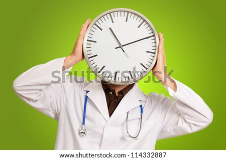 Doctor Hiding Face With Clock On Green Background