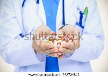 Doctor holding heap of drugs in a hand