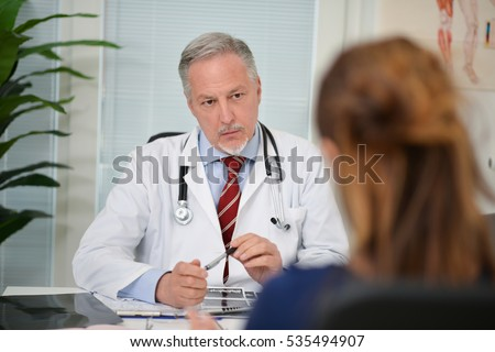 Doctor listening to a patient in his office
