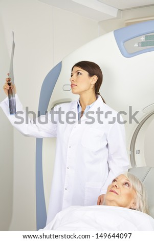 Doctor looking at x-ray image near patient on MRI machine in radiology
